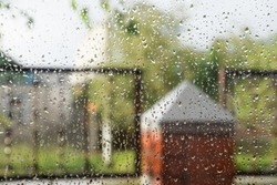 Raindrops on the window pane. Blurred background outside the window in the rain.