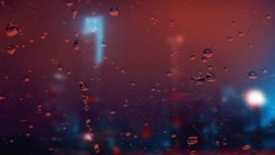 Raindrops on the window. Red and blue lights. Night city.