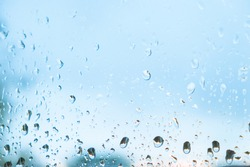 Raindrops on the window. Water droplets on the clear glass surface. Abstract background. Water resistance. Fresh blue backdrop for waterproof products. Showers during the rain season