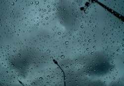 Raindrops on transparent glass against blur dark stormy sky and electric pole. Rain drops on windshield. Windshield window of car with raindrops. Storm day. Sad and depressed abstract background.