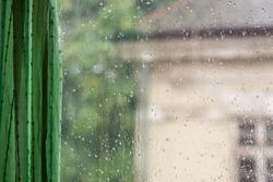 Raindrops on window glass, rainy day, looking trough window