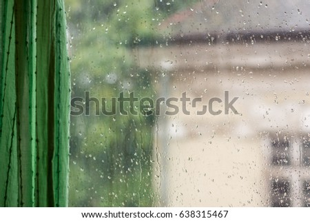 Raindrops on window glass, rainy day, looking trough window