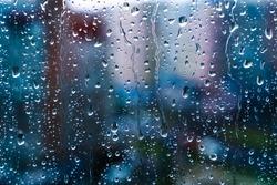 Raindrops on window glass. Selective focus. Rainy city background