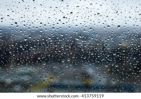 Raindrops or water droplets beaded on the surface of a glass window pane with blurred background #413759119