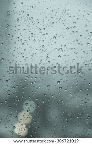 Raindrops over the window with blurred background in vintage green sad tone