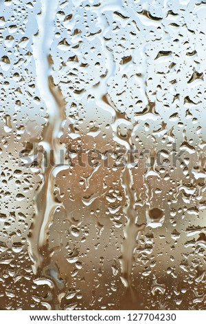 raindrops slide down the window glass, forming abstract figures