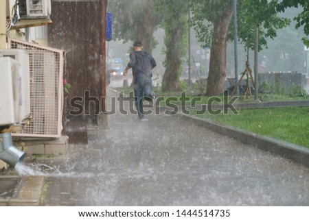 Raining day in the city at summer time. A wet young man running in the rain. Texture of strong, fresh and powerful water drops and sprays. Tropical rains in Moscow as a result of global warming