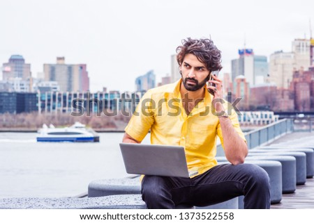 Raining - grainy, drizzling, wet feel. Young Man with beard traveling, working in New York, wearing short sleeve yellow shirt, sitting by East River, working on laptop computer, talking on cell phone.