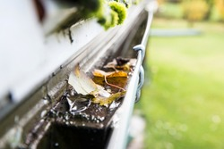 Rainwater gutter cleaning concept, lot of autumn leaves in metal gutter.