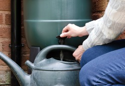rainwater tank or water butt, woman filling watering can with water from the water butt tap.