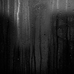 Rainy background with flowing down water drops on window glass