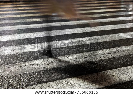 Rainy city street reflections: One young fragile female disappearing while crossing the wet street in the sparkling night