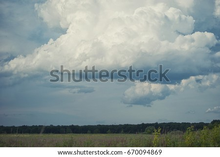 Rainy cloud over green fields and hills. #670094869