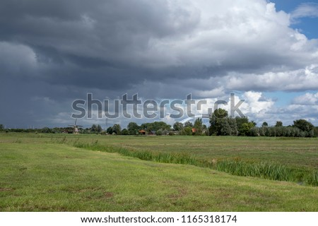 Rainy cloudy sky above a bright green pasture, meadow, and a small creek in it, with at the horizon a dutch wind mill and the new railway bridge over the Amsterdam-Rijnkanaal in the Netherlands.