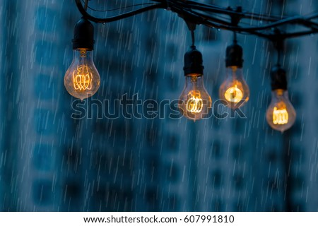 Rainy day at the modern city street. Light bulbs garland against urban buildings background.