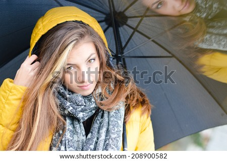 rainy day: closeup on young beautiful brunette woman having fun with umbrella wearing warm yellow coat or puffer on copy space outdoors background, portrait