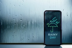 Rainy Day Concept. Weather Information Forecast show on Mobile Phone Screen. View from Inside, through Glass Window