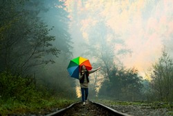 Rainy day. Happy woman with colorful umbrella in forest. Woman walking in the forest with umbrella on a rainy day. Happy girl enjoying rainfall. Concept of nature and happy life