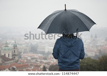 Rainy day in Prague - young man with umbrella