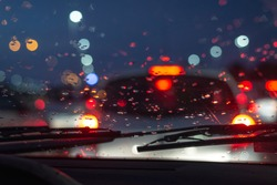 Rainy day in the car view on car traffic jam on rainy day at night traffic lights bokeh with raindrops on carglass