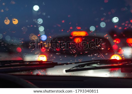 Rainy day in the car view on car traffic jam on rainy day at night traffic lights bokeh with raindrops on carglass  Foto stock ©