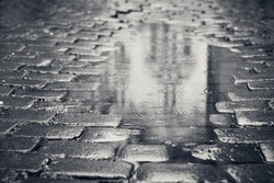 Rainy day. Reflection of the building in puddle on the city street during rain.