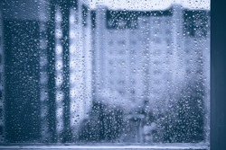 rainy droplets on a blue window glass transparent surface. drops on window shield in a rainy days  in night city. stormy weather. isolation sad depression concept.  rainy season. stay home.