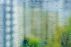 rainy droplets on a wet window glass transparent surface. drops on window pane in a rainy days in the city. stormy weather. isolation sad depression concept. rainy season. buildings houses.