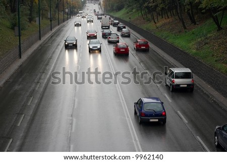 Rainy main road with cars passing by