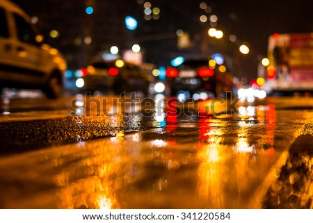 Rainy night in the big city, dense traffic at a busy intersection. View from the level of asphalt