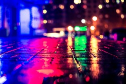 Rainy night in the big city, light from the night club and the windows of the house is reflected in the asphalt. View from the sidewalk level paved with bricks, image in the yellow-blue toning