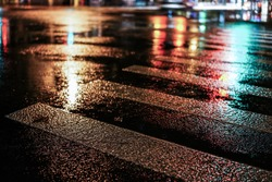 Rainy night in the big city, light from the shop windows reflected on the road on which cars travel. View from the level of asphalt.