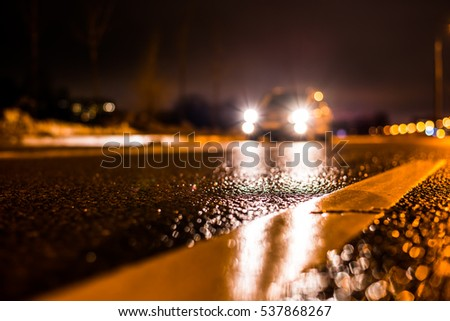 Rainy night in the big city, the car traveling on the highway and shines a blinding light. Close up view from the level of the dividing line #537868267