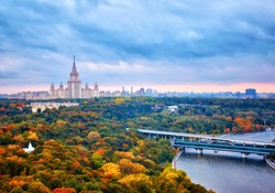 Rainy sunset clouds above river, park, bridge, ships and large city landscape of autumn Moscow