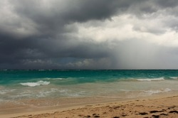 Rainy tropical storm coming from the atlantic ocean to the caribbean shore. Gloomy dark cloudy sky, turbulent sea waves. Empty overcast beach just before the wild rainfall