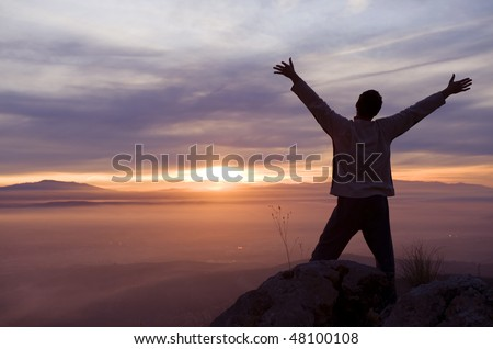 Raised arms man against beautiful sunset