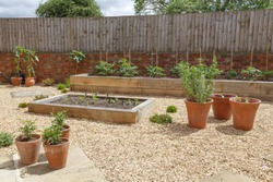 Raised beds in a kitchen vegetable garden with hard landscaping, gravel, terracotta plant pots and raised beds