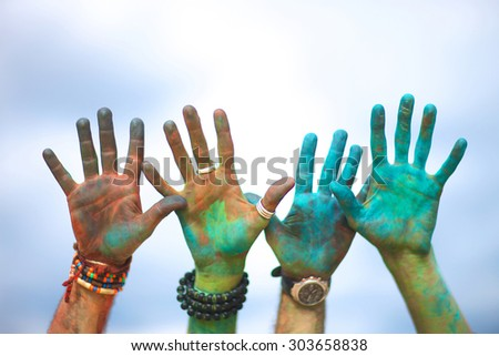 Raised colorful hands at holi festival