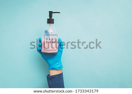 Raised hand holding a bottle of hand soap on blue background