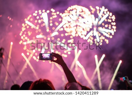Raised hand with shooting horizontal night fireworks sky video smartphone . Colorful bright background entertainment with light and laser show.