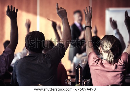 Raised hands and arms of large group of people in class room, audience voting in professional education surrounding, selective focus with anonymous people.