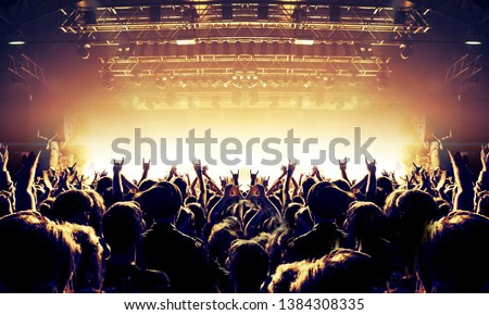 Raised hands in front of a concert stage for a festive crowd #1384308335