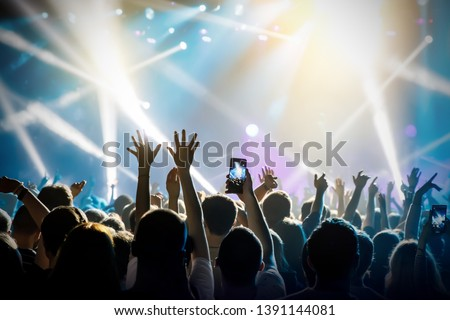 Raised hands in honor of a musical show on stage, People in the hall #1391144081