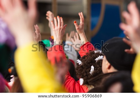 raised hands of cheering people at the street carnival