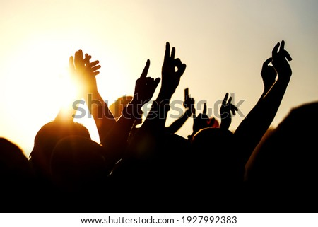 Raised hands of many people at a big mass event. Stockfoto ©
