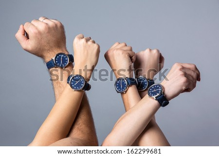 Photo of Raised up human hands in a  spontaneous movement  of unity wearing identical watches