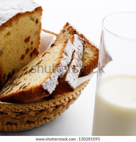 Raisin cake slices with powder sugar and glass of milk on white