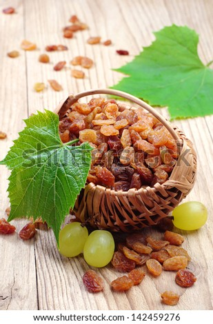 Raisin in a wicker basket and grapes with leaves on wooden table