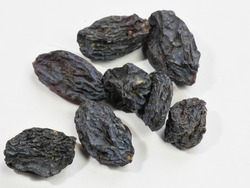Raisins, black. Isolated on a white background. Close-up. Space for text. Macrophotography.