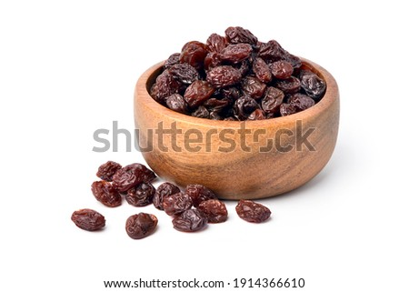 Raisins in wooden bowl isolated on white background. Stock photo ©